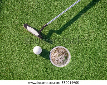 A golf club and a ball during a mini golf game