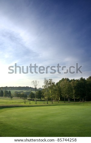 a golf course green with flag at dawn - stock photo