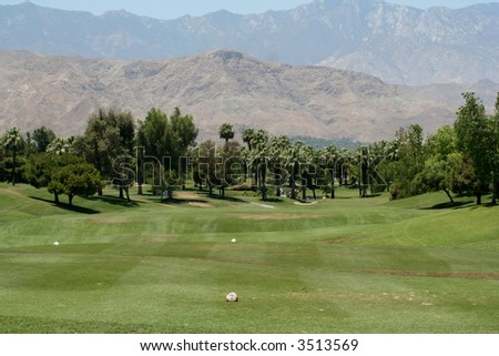 A golf course in Palm Desert, CA with trees and mountains in the background