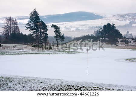 A golf course in Scotland on a snowy winter morning shortly after sunrise. - stock photo