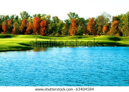 a golf course in the fall with lake - stock photo