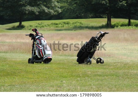 A Golf Course with Two Bags and Their Clubs. - stock photo