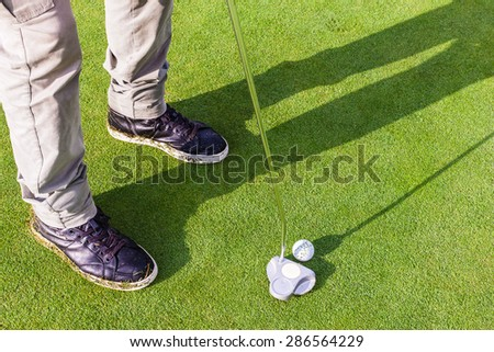 a golf player aiming for the hole on the green with a putter