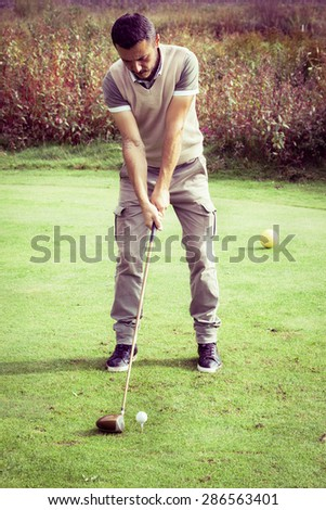 a golf player making a swing on a vibrant beautiful golf course