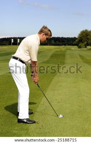 A golf player strikes a shot - stock photo