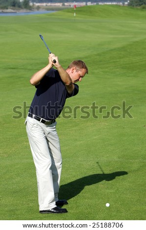 A golf player strikes a tee shot