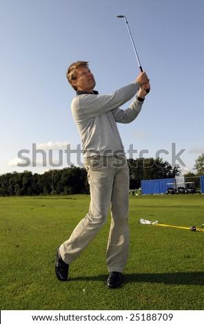 A golf player strikes a tee shot - stock photo