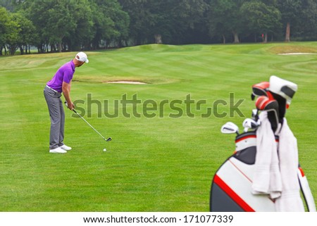 A golfer addressing the ball on a par 4 fairway, series of 3. Focus is on the golfer. - stock photo