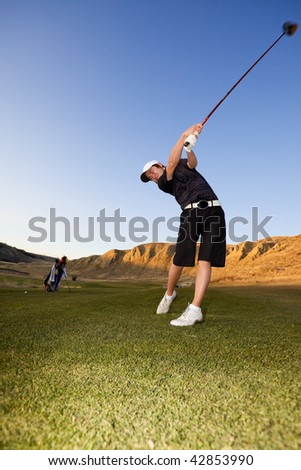 A golfer driving the ball down the fairway - stock photo