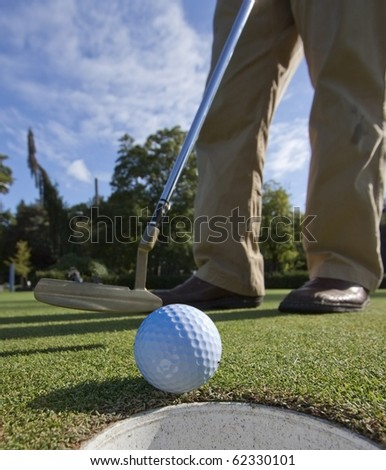 A golfer, having missed the putt by inches, has to tap in.