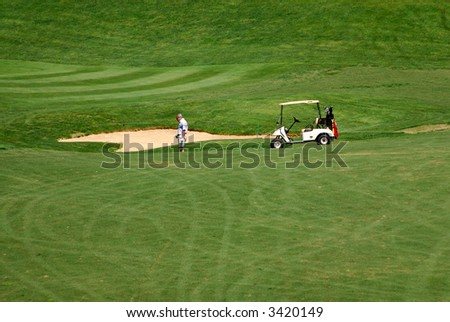 A golfer heads down the hill to find his golf ball in the sand. - stock photo