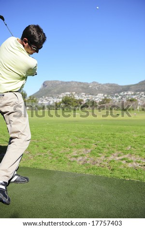 A golfer in action on a practice or driving range, hitting the ball with a club. - stock photo