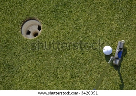 a golfer lines up his putt - stock photo