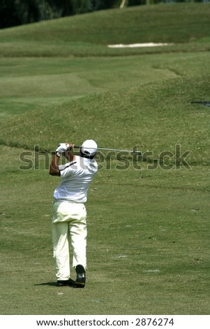 A golfer playing golf in the field. - stock photo