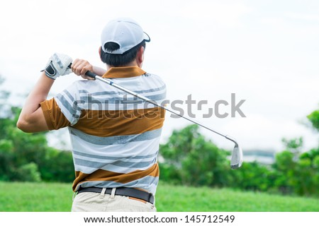 A golfer playing golf viewed behind outdoors - stock photo