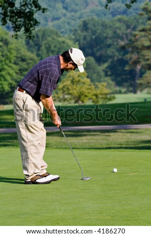 A golfer practicing a putt.  Early evenng sun. - stock photo