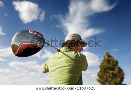 A golfer swinging a large wood (focus on golf club)