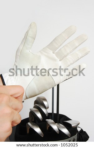 A golfer who is putting on a golf glove