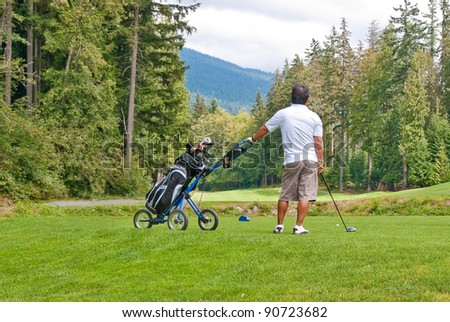A golfer with pull cart. - stock photo