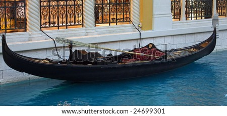 A gondola sitting in a canal of blue water. - stock photo