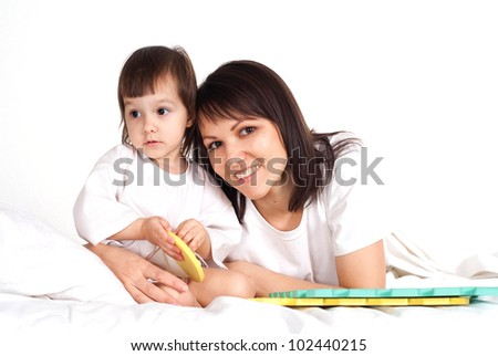 A good Caucasian mother with her daughter play with a mat in the bed