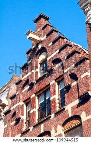 """A good example of the the Dutch trapgevel or """"stair-stepped"""" gable.  This is one of the old converted warehouses that borders a canal in central Amsterdam. - stock photo"""