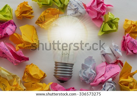 A good idea is like a light bulb that shines,On white background  and  crumpled colorful paper - stock photo