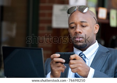 A good looking African American business man works on his laptop or netbook computer with a smart phone in his hands. - stock photo