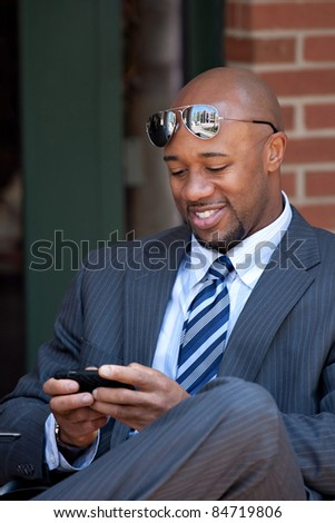 A good looking African American business man works on his smartphone with a smile on his face. - stock photo