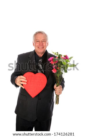 A good looking business man holds Valentine's Day Flowers and Chocolates in a red heart shaped gift box as a gift or gesture of love and affection. Isolated on white with room for your text - stock photo