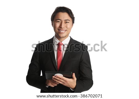 A good looking businessman wearing a black suit, white shirt and a red tie. Holding a digital reader, swiping with his finger. White background. - stock photo