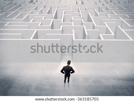 A good looking businessman with briefcase standing in front of white labirynth entrance about to make a decision concept - stock photo