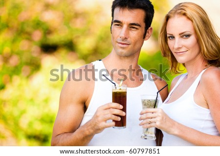 A good looking caucasian couple relaxing with cocktails outdoors
