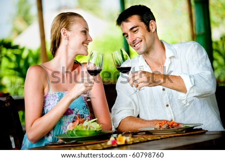 A good looking couple having a meal with wine at a restaurant - stock photo