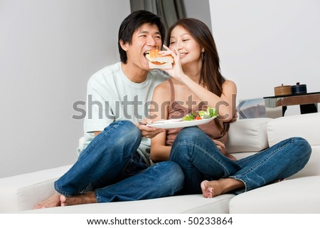 A good looking couple having a sandwich on their couch at home - stock photo