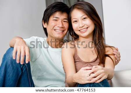 A good looking couple relaxing on their couch at home - stock photo
