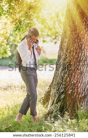 A good looking grey hair business man is standing naked feet in the grass, answering his phone.He is relaxing, enjoying the shadow of the tree in a sunny day. - stock photo
