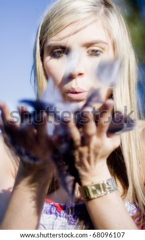 A Good Looking Lady Blows A Kiss While Holding Onto A Handful Of Feathers In A Sexy Motion Of Love - stock photo