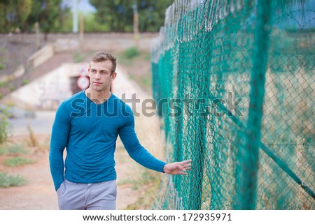 A Good looking male model walking past a fence, wearing trousers and a long sleeved t-shirt - stock photo