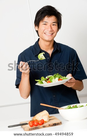 A good looking man eating a healthy meal of bread and salad in his kitchen - stock photo