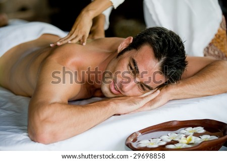 A good-looking man getting a back massage lying down - stock photo