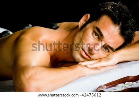 A good looking man lying on a massage bed with hot stones on his back - stock photo
