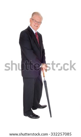 A good looking mature man in a dark suit, glasses, holding a long umbrella standing isolated for white background.