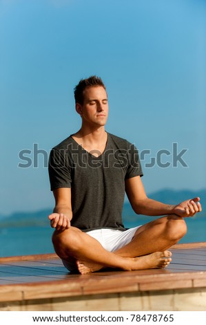 A good-looking young  man doing yoga on a jetty - stock photo