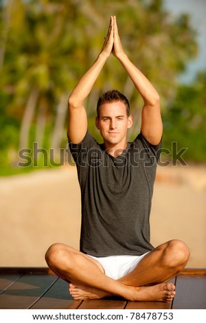 A good-looking young  man doing yoga on a jetty with tropical island backdrop - stock photo