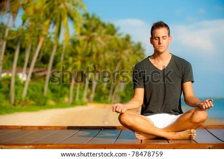 A good-looking young  man doing yoga on a jetty with tropical island backdrop