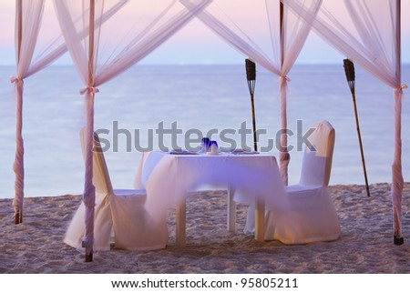A good place for romantic dinner on the beach. Long exposure shot. Focused on a dishware, shallow DOF. - stock photo