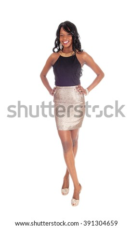 A gorgeous African American woman standing in a gold colored skirt and