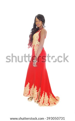 A gorgeous African American woman standing in a long red evening dresswith gold embroideries and long black hair isolated for white background. - stock photo