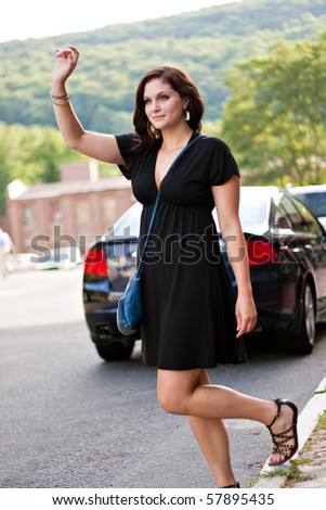 A gorgeous brunette woman hails a cab at the side of the road in the city. - stock photo